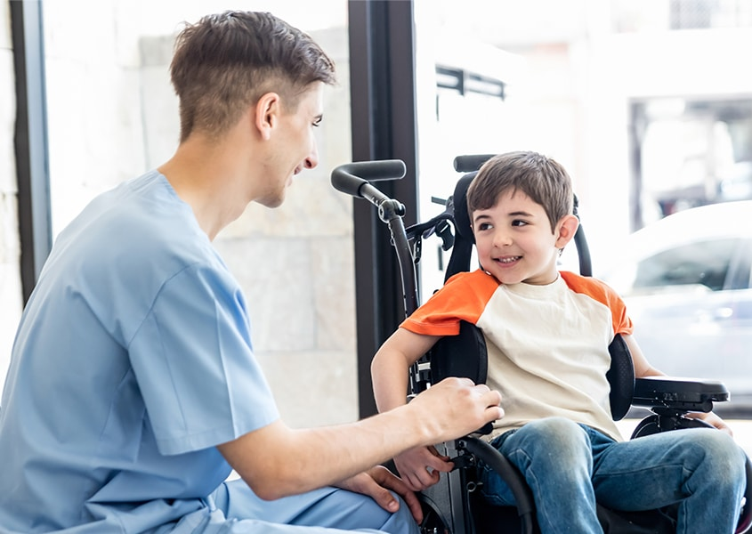 doctor with boy in a wheelcahir smiling