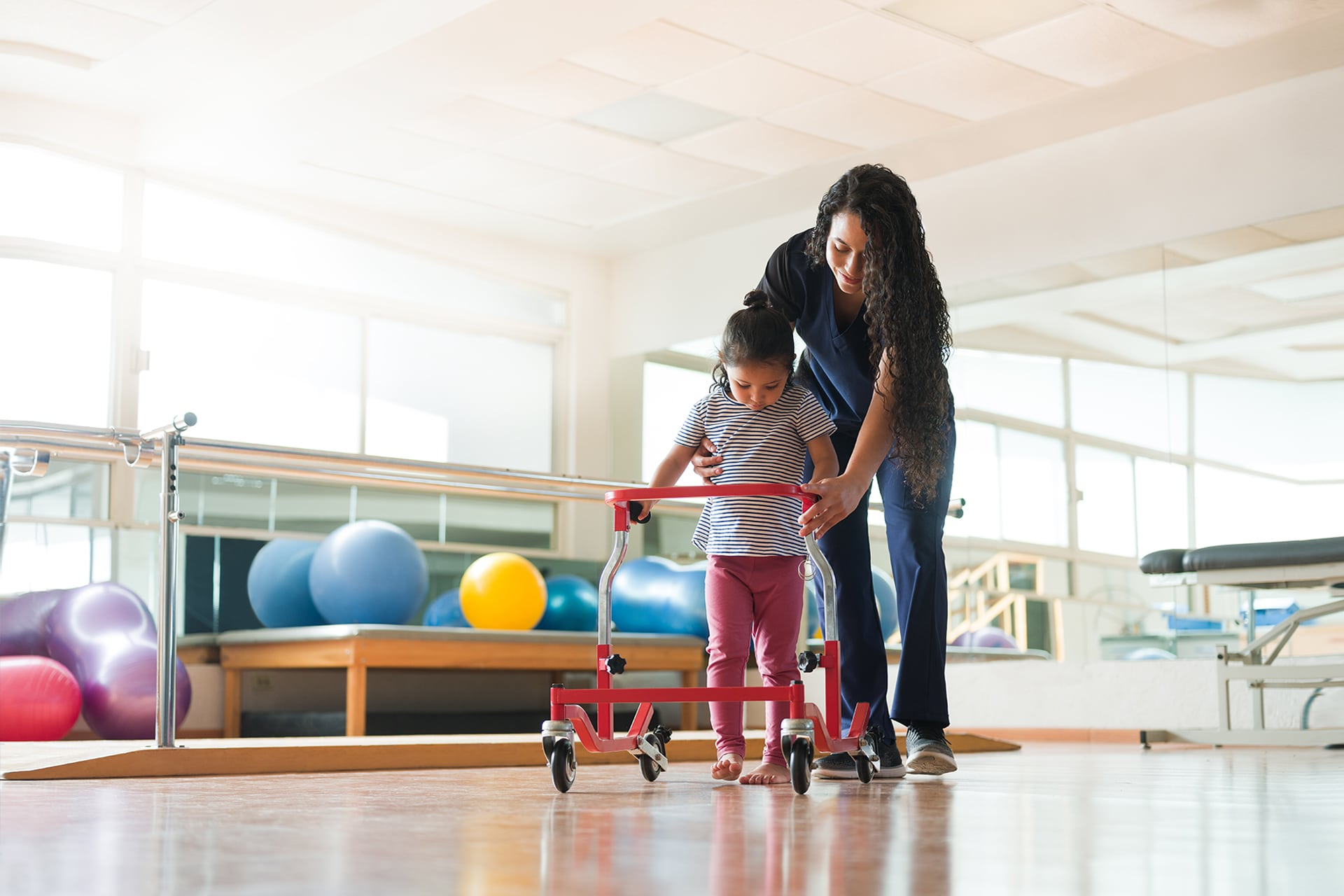 Women physical therapist helping a child learn to walk